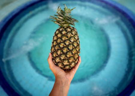 girl holding pineapple in hands near the pool