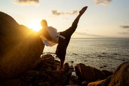 Kerl macht Yoga bei Sonnenuntergang am Meer