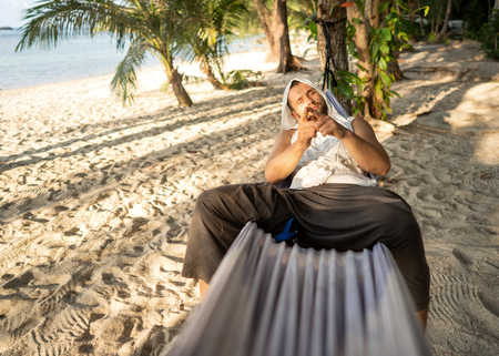 guy is lying on a hammock near the sea in the jungle
