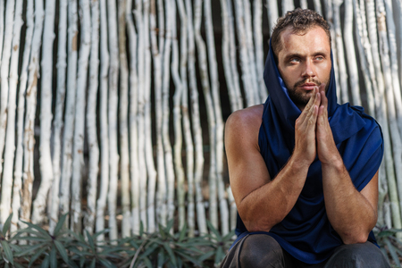 fashion guy makes namaste near bamboo white background, prays.