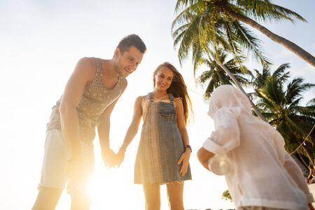 glückliche Familie, die bei Sonnenuntergang spielt Standard-Bild