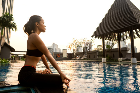 girl meditates at sunset in Thailand near the pool