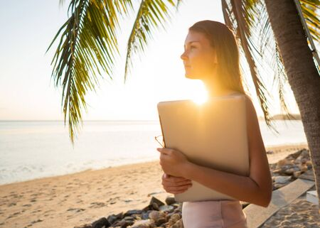 freelancer girl with a computer among tropical palm trees work on the island