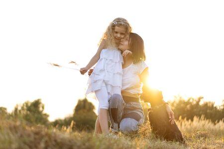 Mutter mit Tochter mit Hund Zwergschnauzer spielt bei Sonnenuntergang Standard-Bild