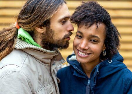 ragazzo con una ragazza africana innamorata che si abbraccia nel parco autunnale a piedi al tramonto
