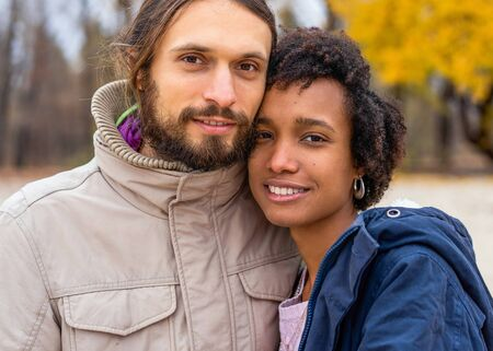 guy with an african american girl in love in autumn park walk at sunset