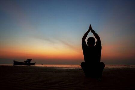 ragazzo al tramonto sull'isola pratica yoga, silhouette