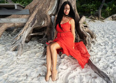girl in a red dress among tropical palm trees in Thailand at sunset