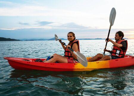 Coppia in kayak insieme. Bella giovane coppia in kayak sul lago insieme e sorridente al tramonto Archivio Fotografico