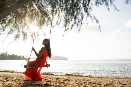 girl in a red dress on a swing among tropical palm trees in Thailand at sunset Imagens