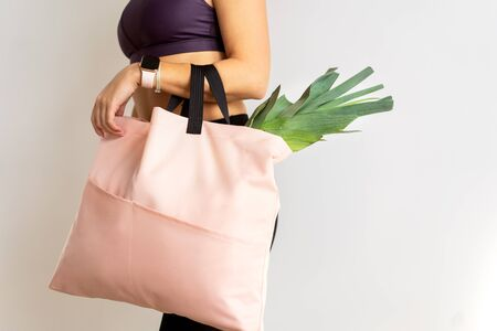 girl with a shopping bag in pink hands with products. Take away, fitness food.