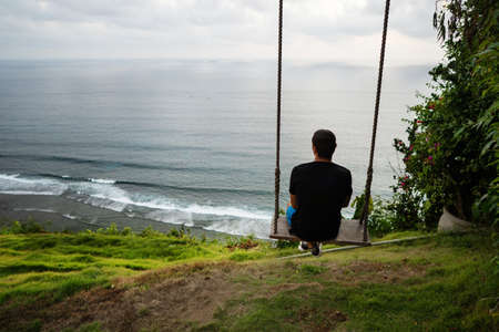 guy sits on a swing on a cliff by the ocean at sunset in bali Reklamní fotografie