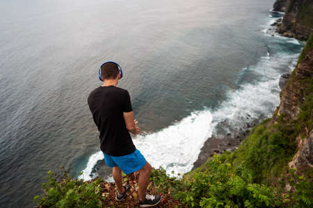 guy in headphones stands on a cliff by the ocean at sunset in bali Reklamní fotografie