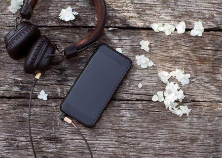 phone with headphones lie on a wooden background Reklamní fotografie