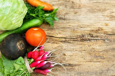 Exposition of fresh organic vegetables on woodetable. Tomatoes, cabbage, radish, cucumber, parsley, black radish, carrot Standard-Bild
