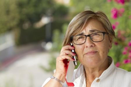 60 years old: Senior woman talking on mobile phone