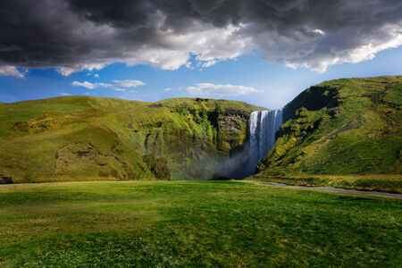 Skogafoss waterfall in Iceland with cloudy sky photo