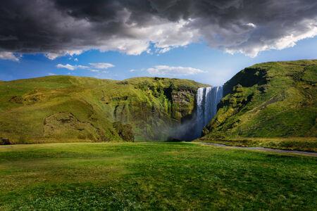 skogafoss waterfall: Skogafoss waterfall in Iceland with cloudy sky