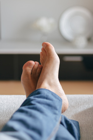 adult foot: Feet of man relaxing on the sofa