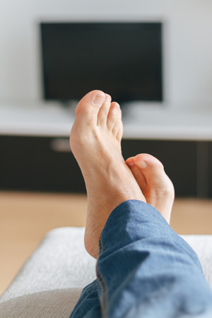 sole on foot: Feet of man relaxing on the sofa