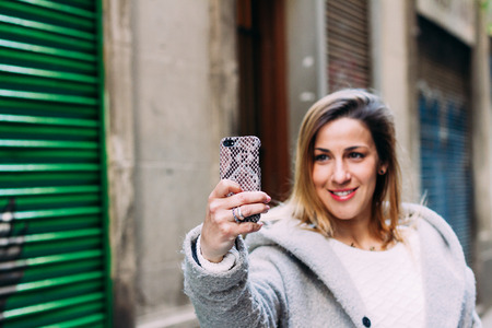 Young beautiful blond woman touching and browsing her smart phone over city background