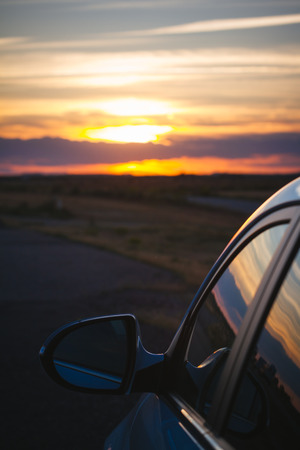 purple car: Rear view mirror at sunset Stock Photo