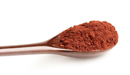 Powdered cocoa in ceramic spoon isolated on white background. Stock Photo
