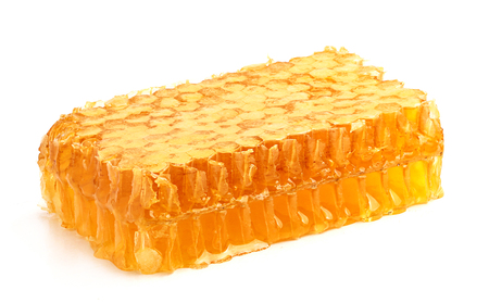 Fresh honey in the comb close-up isoleted on white background.
