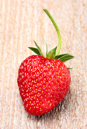 Ripe strawberries closeup on wooden background.