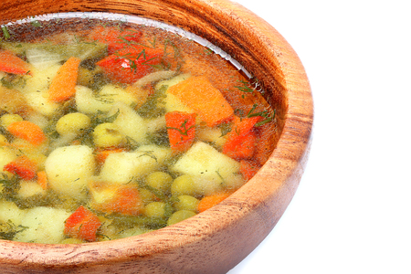 l plate: Homemade soup in a wooden bowl closeup isolated on white background.