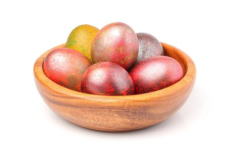 Painted Easter eggs iin wooden bowl isolated on white background. Stock Photo