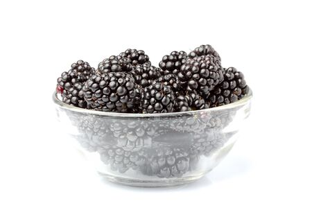 Ripe BlackBerry berries in a glass bowl isolated on white.