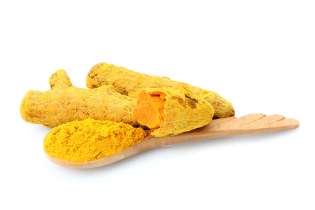 Turmeric root with powder in spoon isolated on white background.