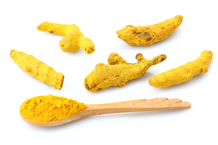 Turmeric rhizome and powder in spoon on white background. Stock Photo