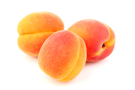 Three apricots isolated close-up on white background. Stock Photo