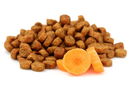 Dry food for dogs and cats with a slice of carrots.Isolated on white background. Stock Photo