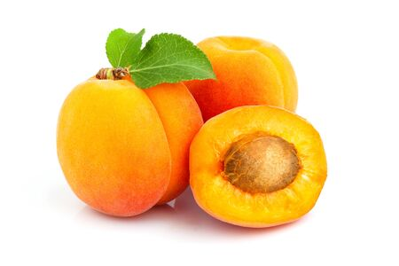 Fresh apricot fruit with leaf and half isolated on white background.