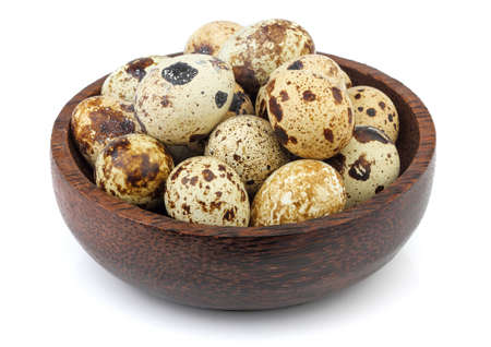 Quail eggs in wooden bowl isolated on white background.