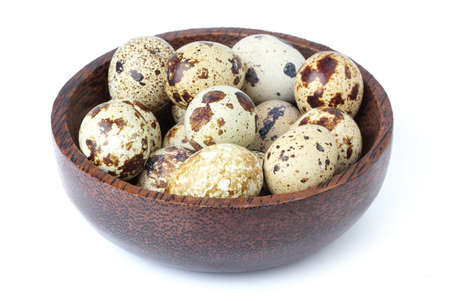 Quail eggs in wooden bowl on white background.