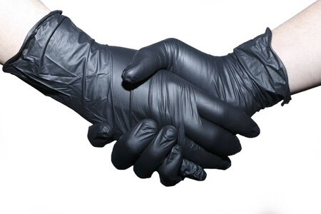 Two people shake hands in black latex gloves. Preventive measures to protect against coronavirus.
