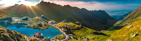 originality: God rays over the mountains. Transfagarasan Balea glacier lake, panoramic view - Lake, is a glacier lake situated at 2.034 m. of altitude in the Mountains, in central Romania, Sibiu County. Stock Photo