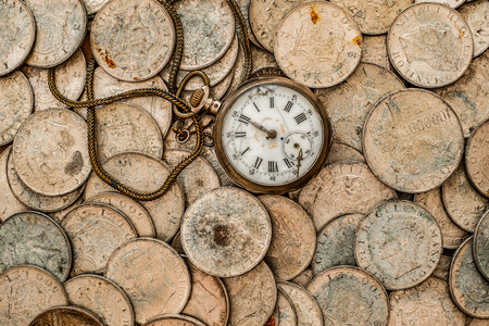 numismatist: Time is money, a bunch of coins with a pocket watch on top, top view, HDR processing in old style.