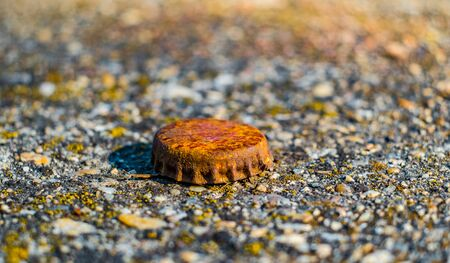 twist cap: Old rusty bottle cap on a concrete with moss.