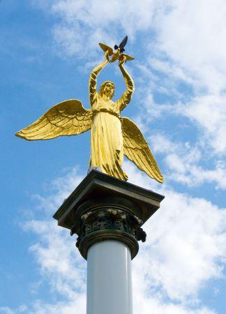 Sculpture of golden angel with pigeon in hands photo