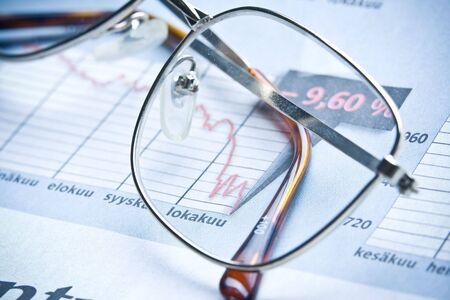 job loss: glasses on financial diagram. business concept