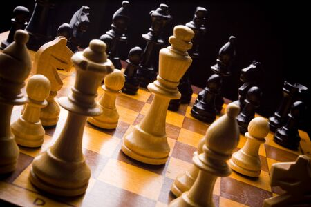 battle plan: Old Craved wooden Chess pieces on a Board Stock Photo