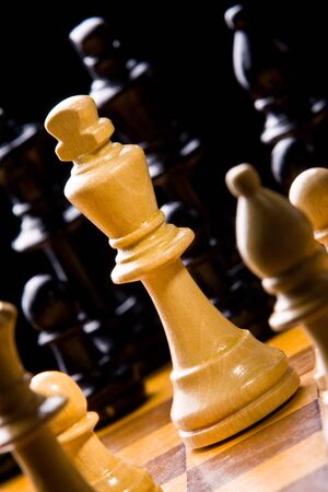 Old Craved wooden Chess pieces on a Board photo