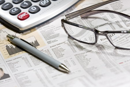 newsworthy: financial newspaper with eye glasses and calculator Stock Photo
