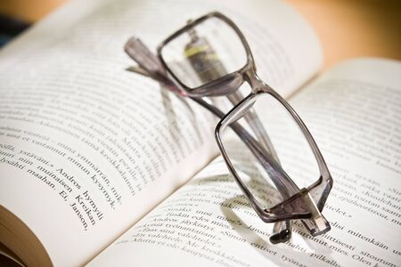 closeup of opened book and glasses photo