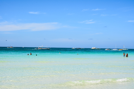 excursions: Some tourists swim and take pictures in the White Beach of Boracay with the boats behind them ready for the excursions. Stock Photo